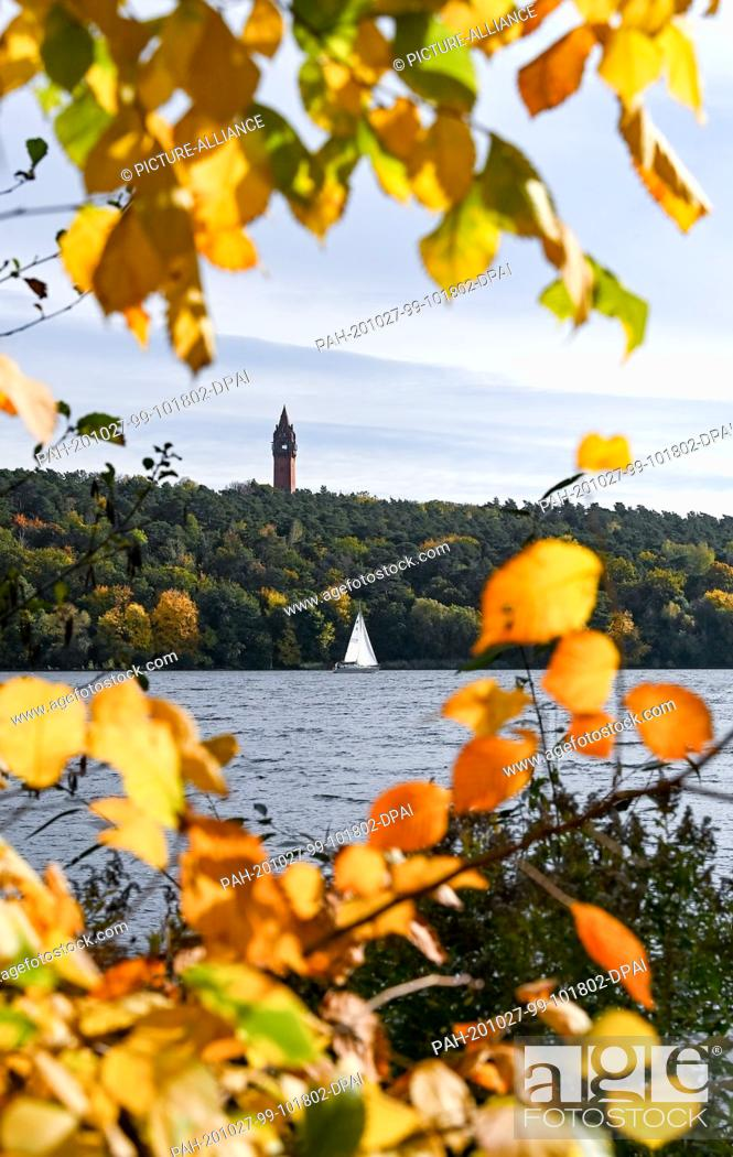 Stock Photo: 27 October 2020, Berlin: In sunny autumn weather, a sailing boat sails past brightly coloured trees and the Grunewald tower near Gatow on the Havel.