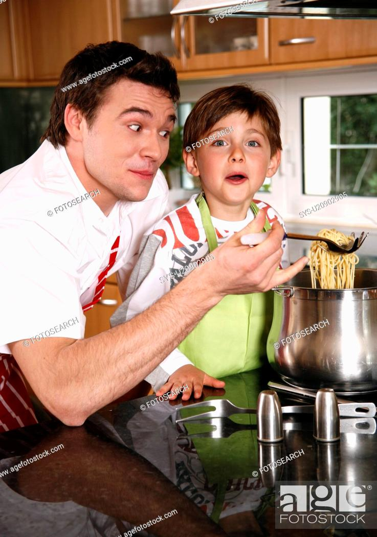 Stock Photo: Father and son cooking spaghetti.