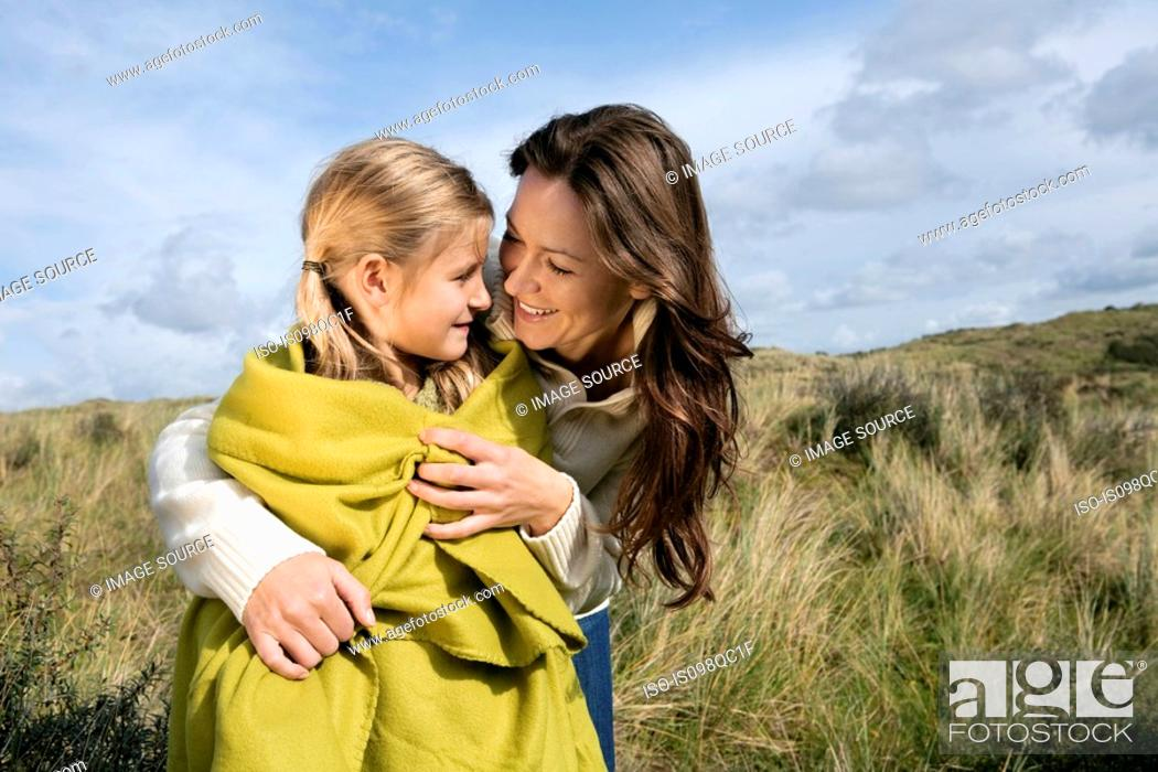Stock Photo: Mother and daughter outdoors with blanket.