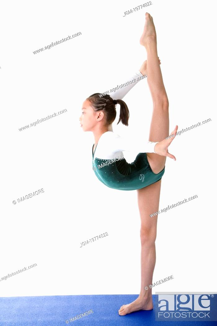 Stock Photo: Girl practicing gymnastic pose on pad, side view.
