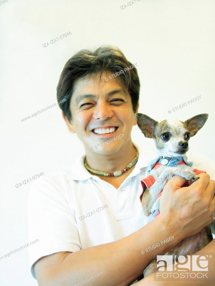 Imagen: Portrait of a mid adult man carrying a Chihuahua puppy.
