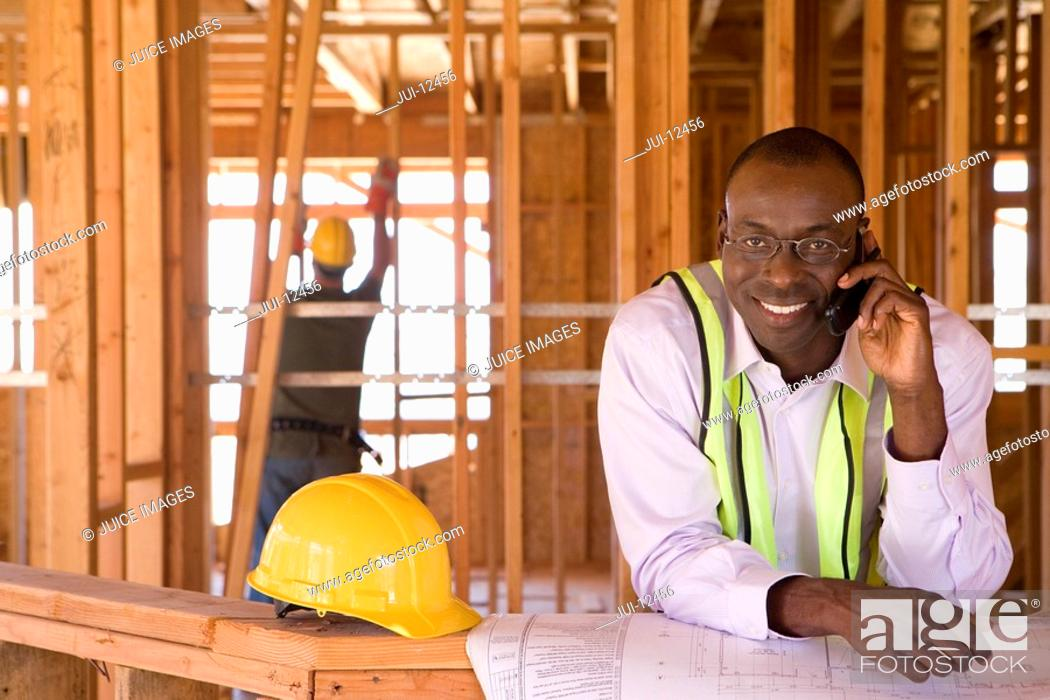 Stock Photo: Businessman with blueprints using mobile phone in partially built house, smiling, portrait.