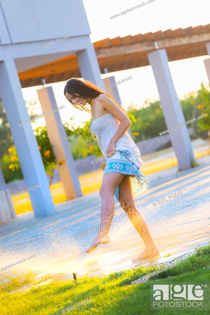 Stock Photo: Playing with meadow sprinkler spray young woman.
