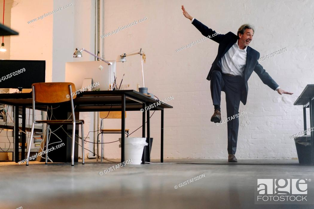 Stock Photo: Happy senior businessman doing gymnastics in office.