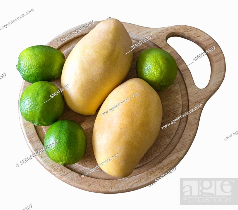 Stock Photo: Mango and lime lie on a cutting board isolated on white.
