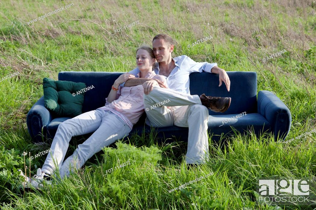Stock Photo: A couple sitting on a sofa in a field of grass.