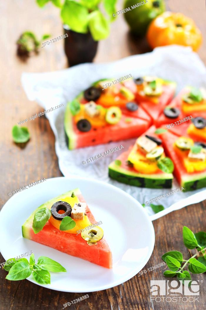 Stock Photo: A piece of melon garnished like a pizza with tomatoes, tofu, olives and fresh herbs.