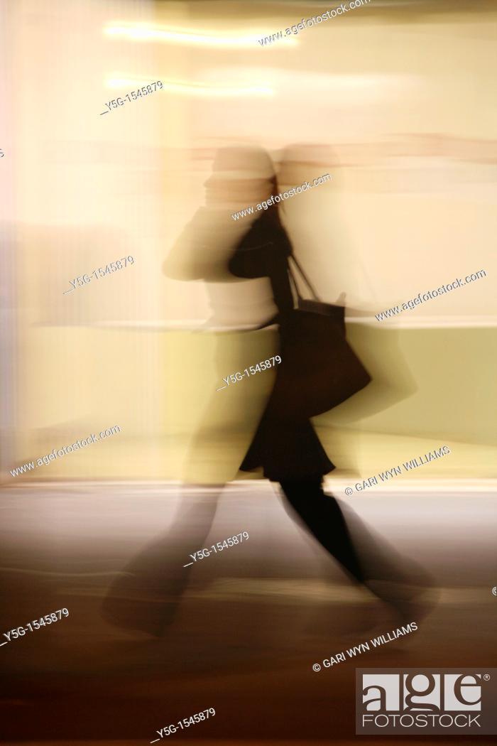 Stock Photo: woman shopper feet legs walking in street in town at night.