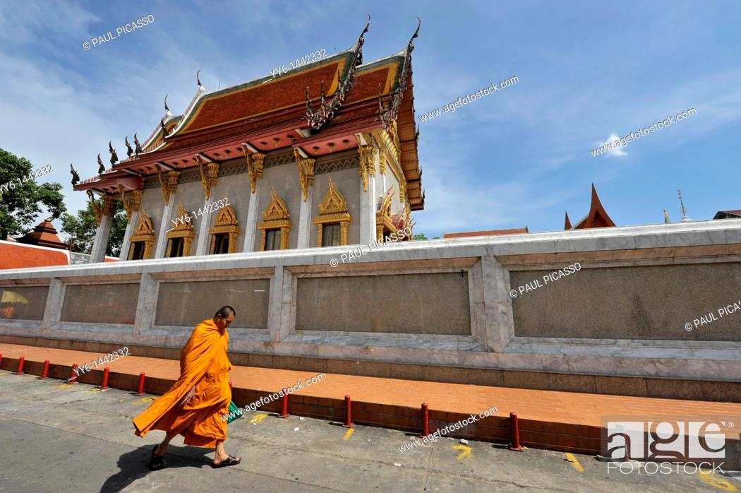 Stock Photo: monk walking past Wat Intharawihan, also known as Wat Indravihan , built during the later Ayutthaya period, is one of the most frequented temples in Bangkok.