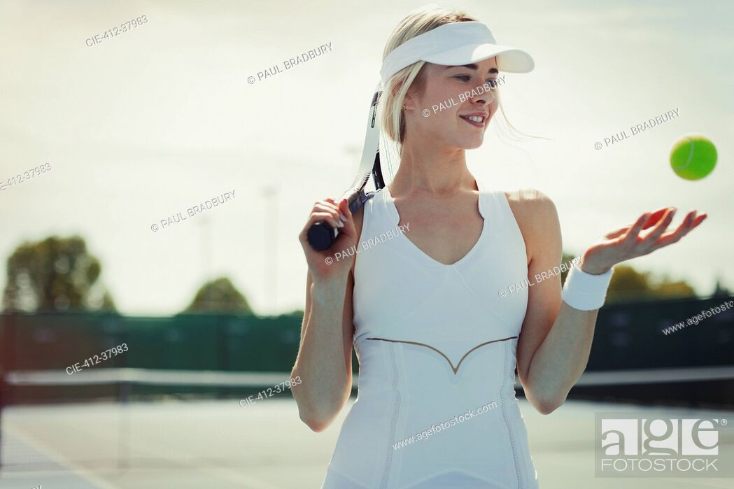 Stock Photo: Smiling young female tennis player holding tennis racket and tennis ball on tennis court.