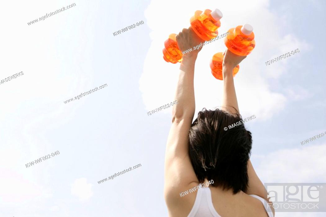 Stock Photo: A woman raises the dumbbells straight up.