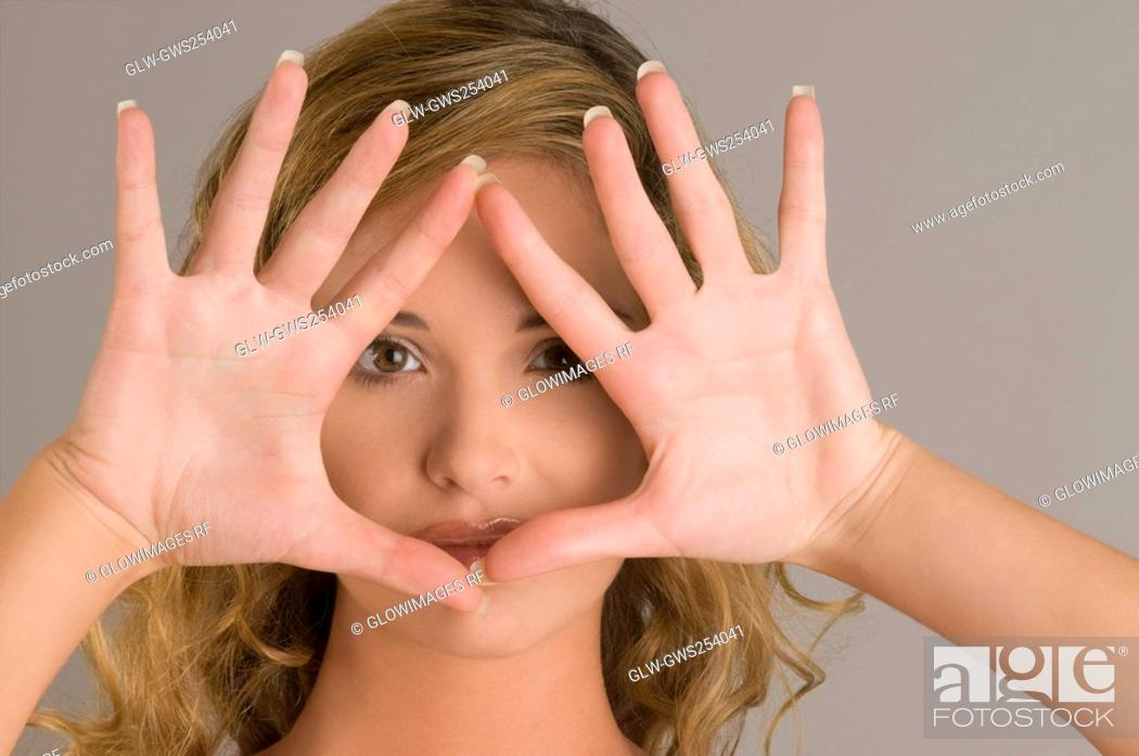 Stock Photo: Portrait of a young woman with her hands over her face.