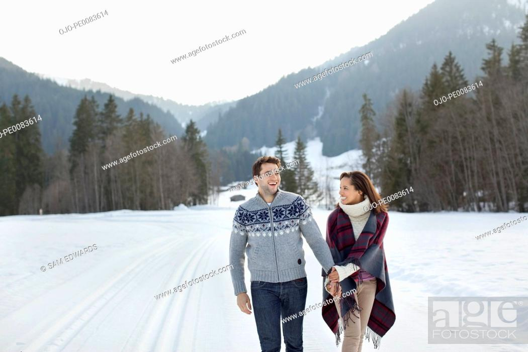 Stock Photo: Smiling couple holding hands and walking in snowy field.