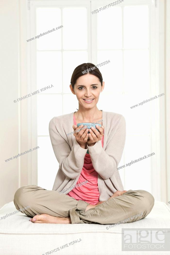 Stock Photo: Germany, Berlin, Mature woman holding bowl, smiling, portrait.