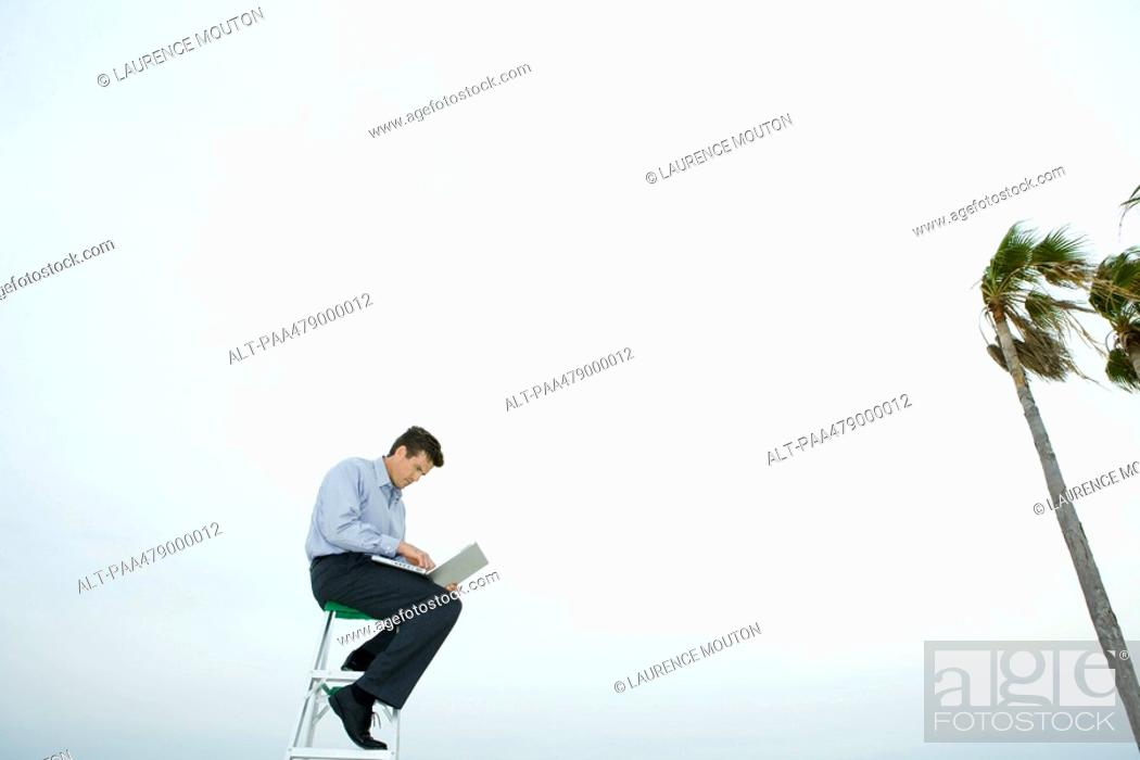 Stock Photo: Man sitting in wind, using laptop, low angle view.