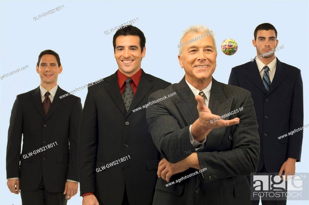 Stock Photo: Businessman catching a rubber band ball with three businessmen standing behind him.