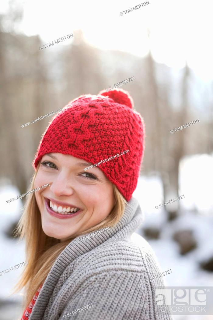 Stock Photo: Close up portrait of smiling woman with red knit hat.