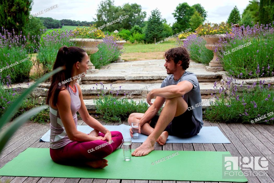 Stock Photo: Man and woman practicing yoga in garden, taking a break on patio.