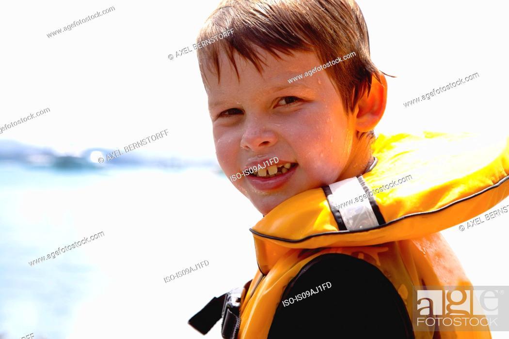 Imagen: Close up portrait of smiling boy in lifejacket.