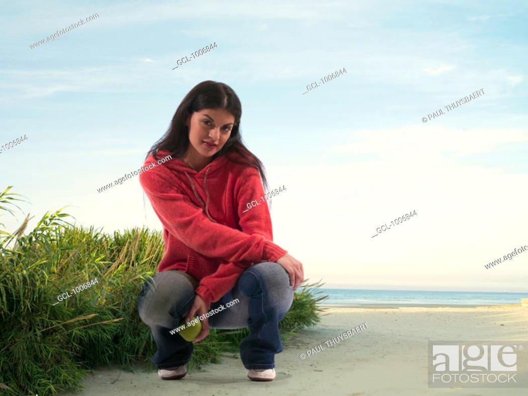 Stock Photo: Woman with apple on the beach in Jebel Danah, Abu Dhabi, UAE.