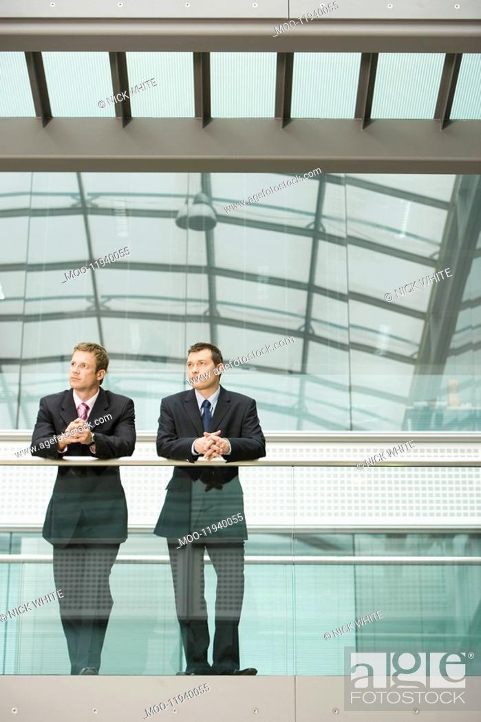 Stock Photo: Two Businessmen Leaning at Railing front view.