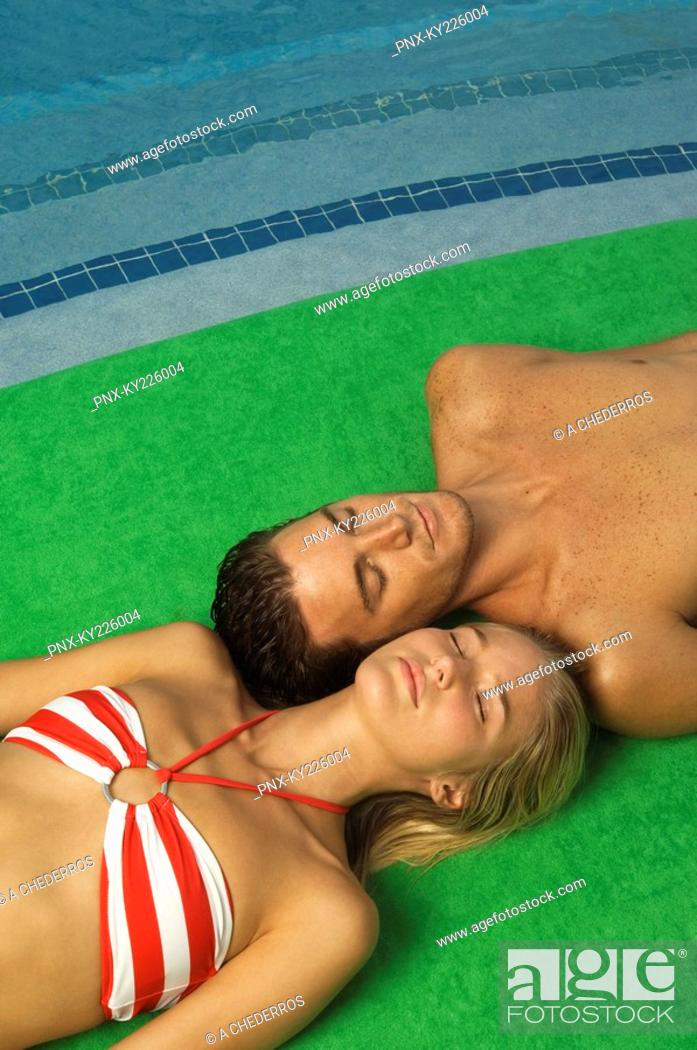 Stock Photo: Couple sunbathing at the poolside.