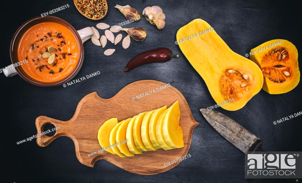 Stock Photo: fresh pumpkin chopped and thick soup in a ceramic plate on a black background, top view.