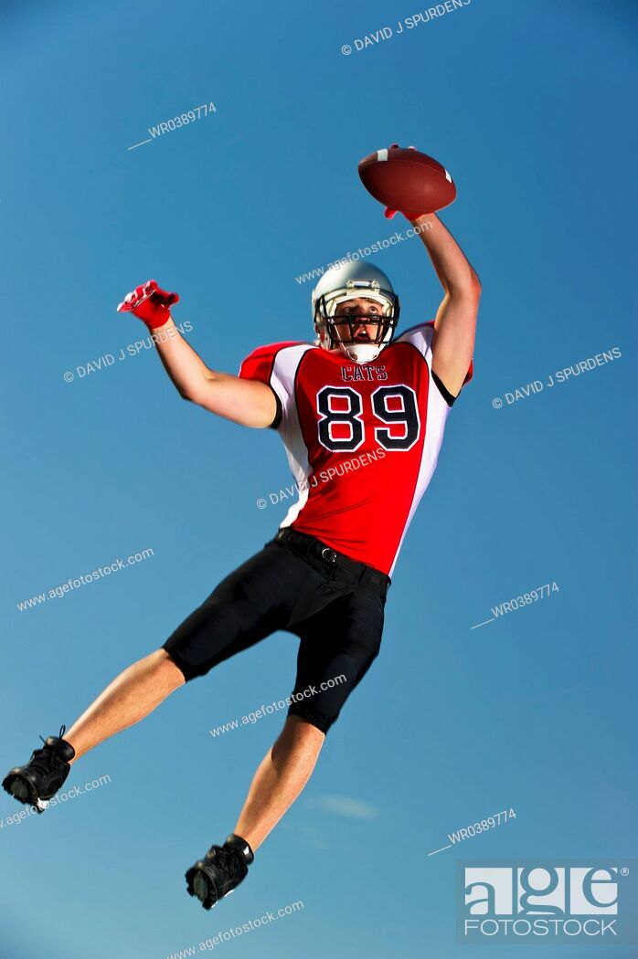 Stock Photo: American Football player jumps high to make the catch.