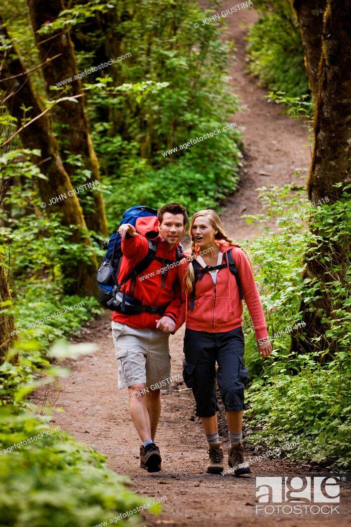 Imagen: Portland, Oregon, USA, Couple walking on trail through forest.