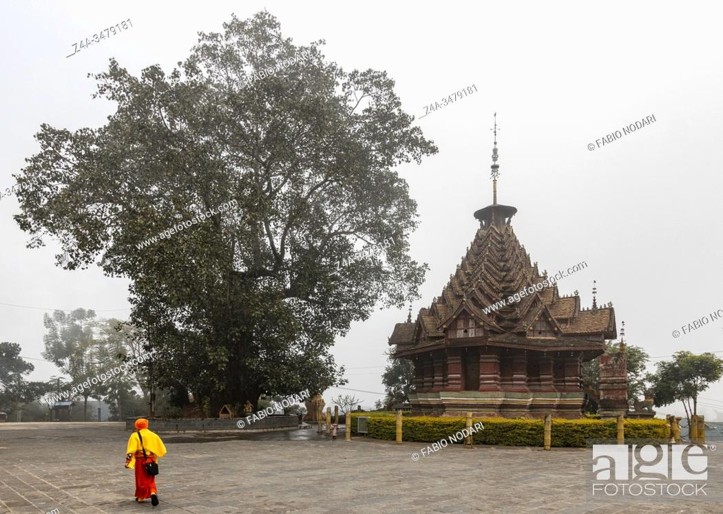 Stock Photo: Jinghong, China - December 31, 2019: Octagonal Pavilion Jingzhen Bajiao Ting in Xishuangbanna and monk on foreground.