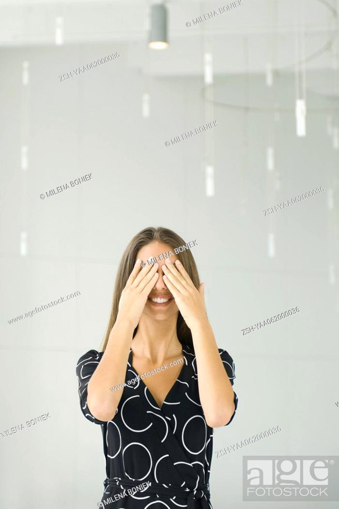 Stock Photo: Teenage girl covering eyes with hands, smiling, front view.