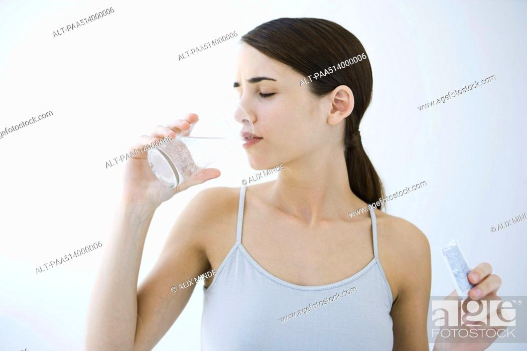 Stock Photo: Woman drinking effervescent water, holding medicine packet.