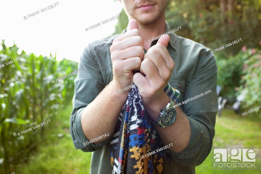 Photo de stock: Cropped shot of mid adult man folding blanket in field.