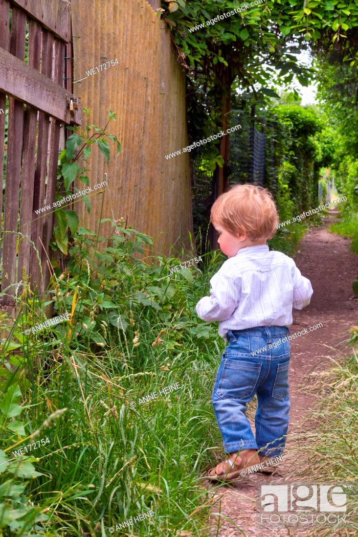 Stock Photo: Toddler walking along alley seen from behind. Graurheindorf in Bonn, Germany.