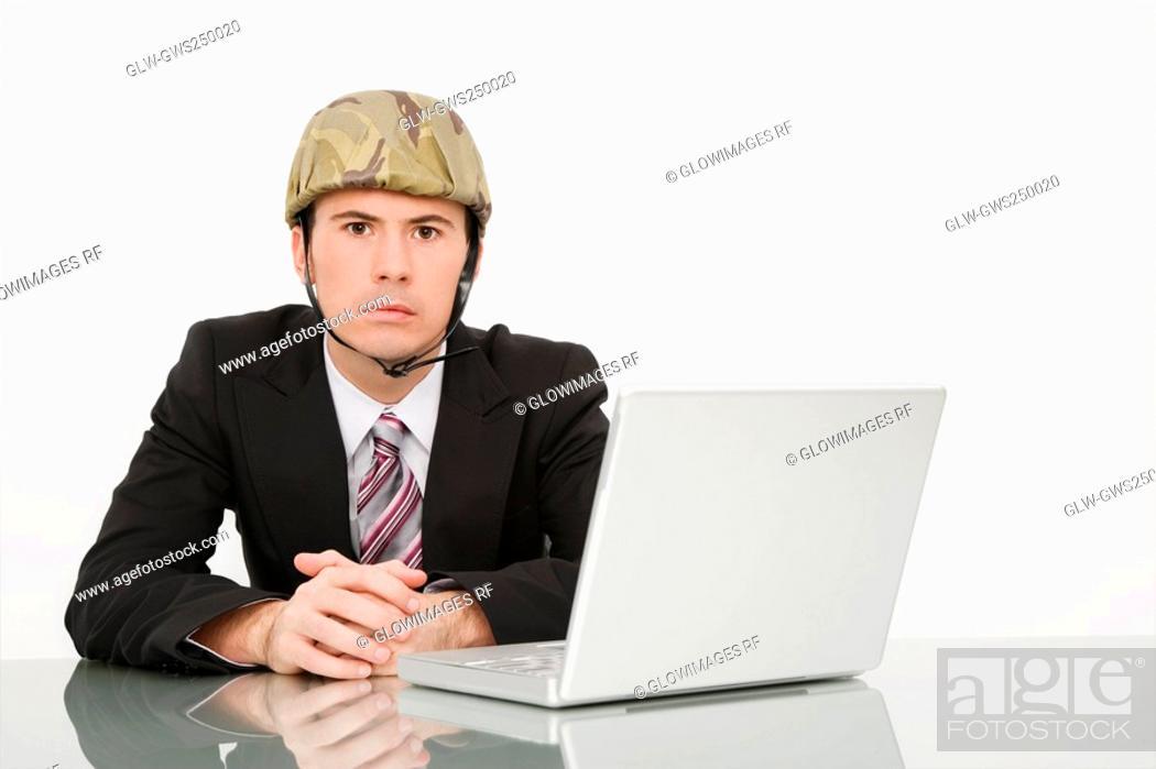 Stock Photo: Portrait of a businessman wearing an army helmet.