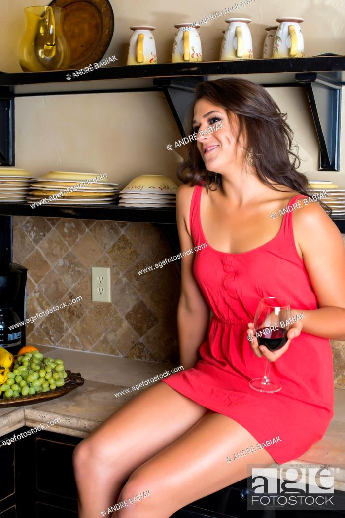 Stock Photo: USA, Texas, Young woman with wine glass sitting on kitchen worktop.