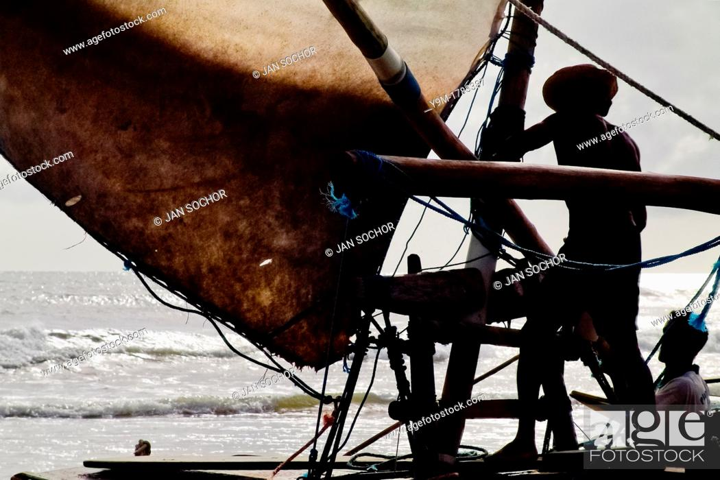 Stock Photo: Brazilian fisherman attaching the sail to the wooden yard during the sunrise in Uruau, state Ceara, Brazil, 16 March 2004  Fishermen use a unique wooden raft.