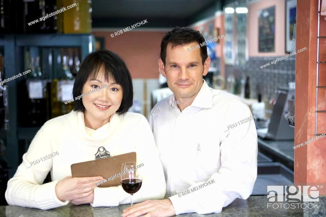 Stock Photo: Man and woman at counter in winery, portrait.
