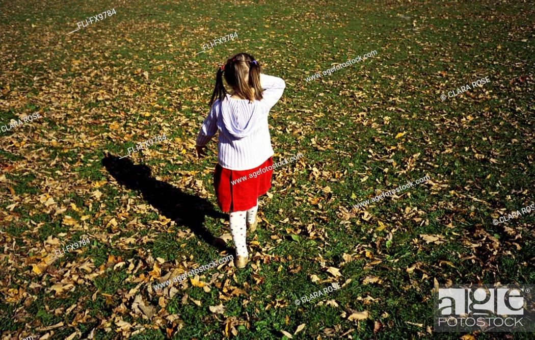 Stock Photo: Little girl walking on the grass covered with falling leaves, Montreal, Quebec.