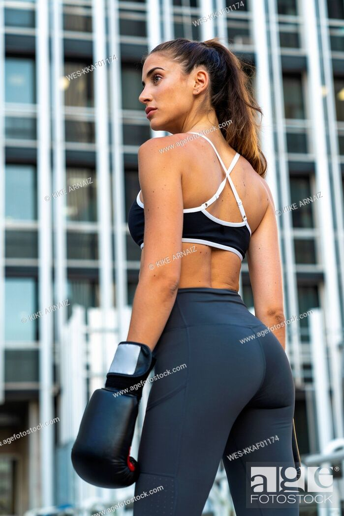 Photo de stock: Sportive young woman with boxing gloves in the city in front of a high-rise building.