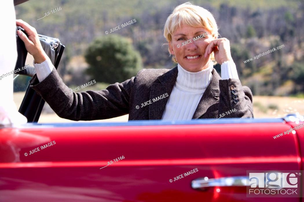 Stock Photo: Senior woman posing with red convertible.