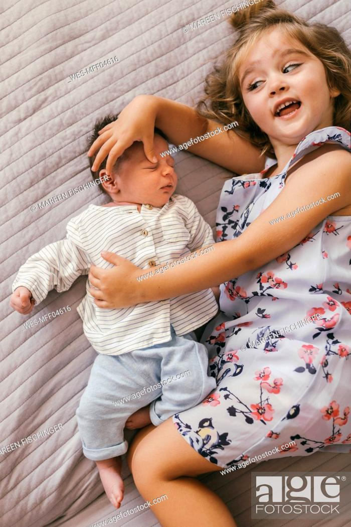 Stock Photo: Playful girl lying on blanket cuddling with her baby brother.