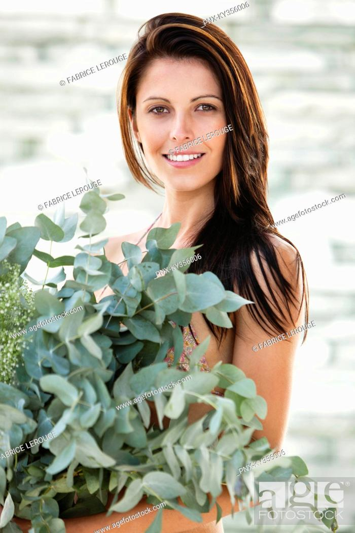 Stock Photo: Portrait of a woman holding leaves and smiling.