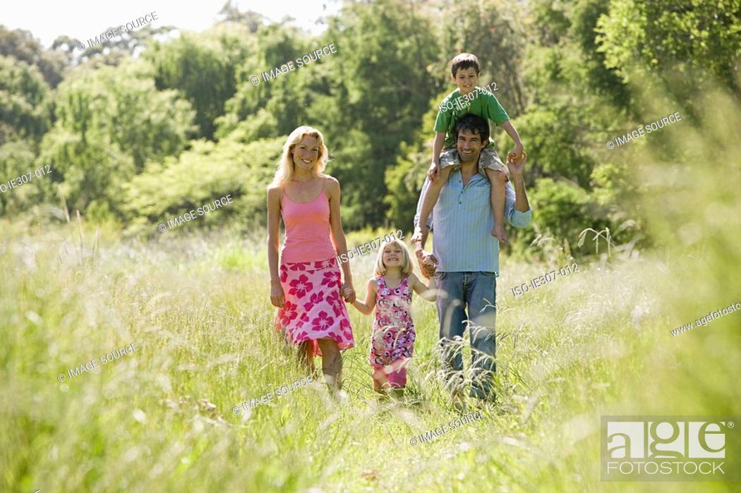 Stock Photo: A family walking through a field.