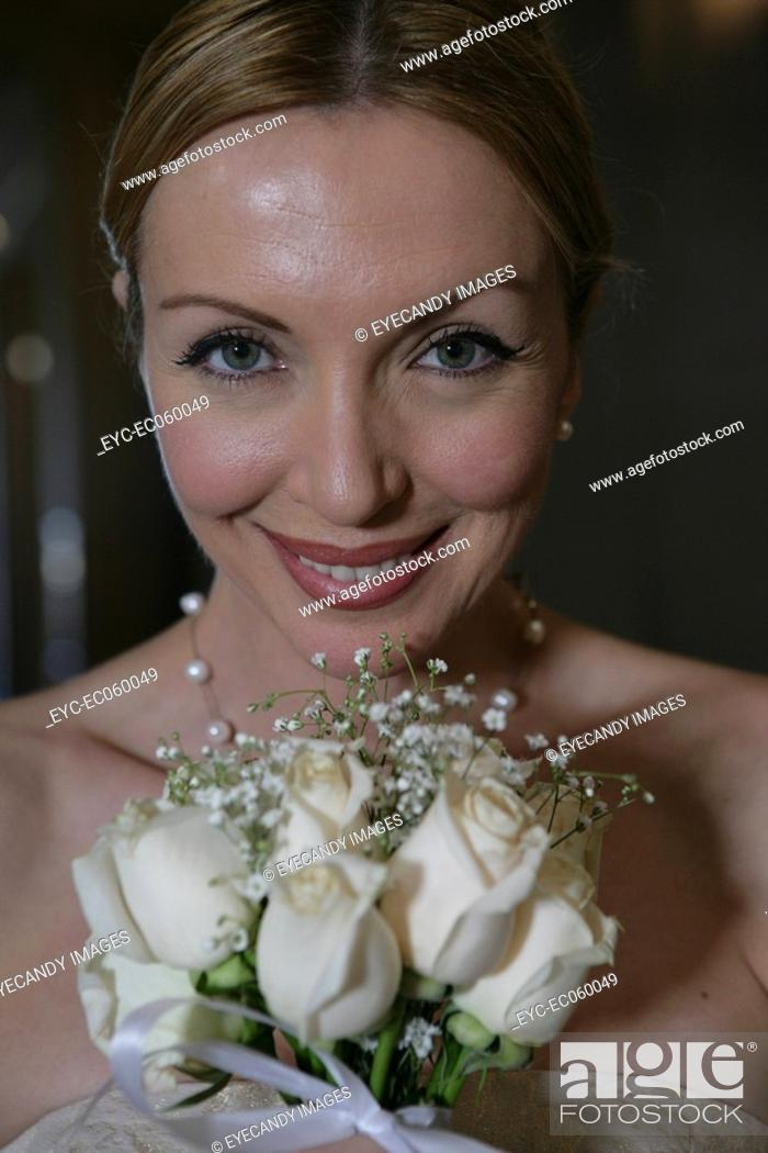 Stock Photo: Mature women holding a bouquet of white roses.