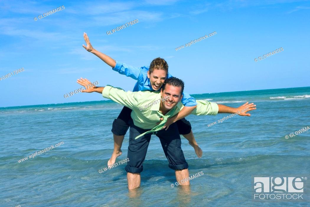 Stock Photo: Mid adult woman riding piggyback on a mid adult man with their arms outstretched on the beach.
