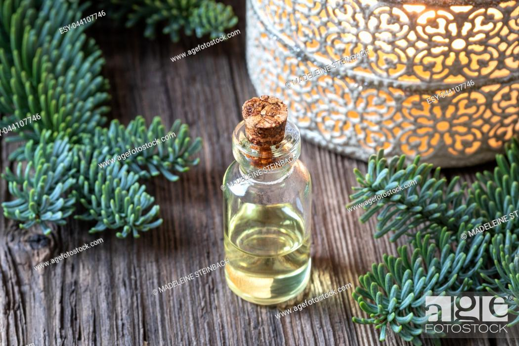 Stock Photo: A bottle of essential oil with fresh fir branches.
