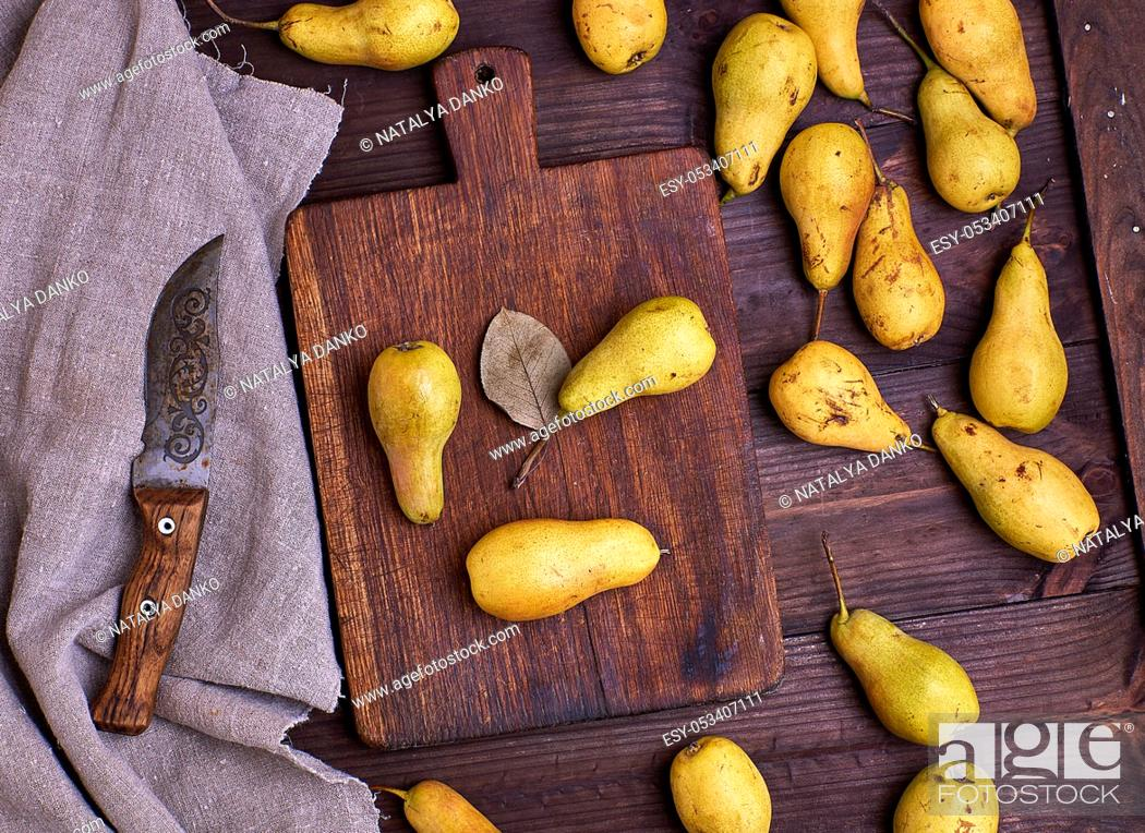 Stock Photo: ripe yellow pears scattered on a brown wooden table, top view.
