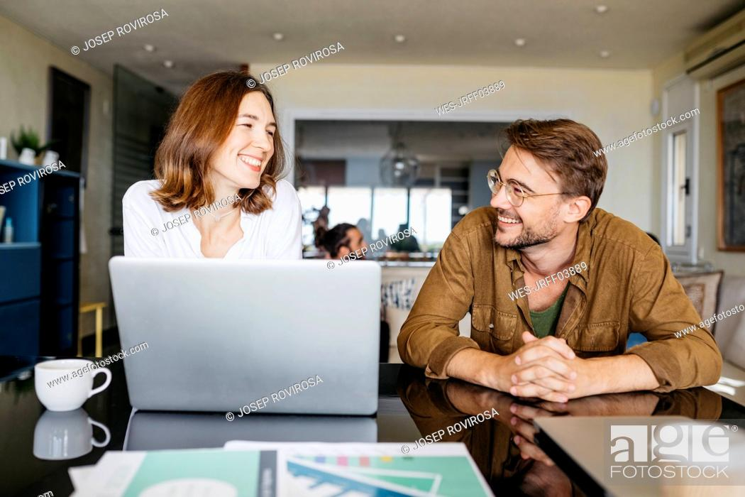 Stock Photo: Happy man and woman working together with laptop on table at home.