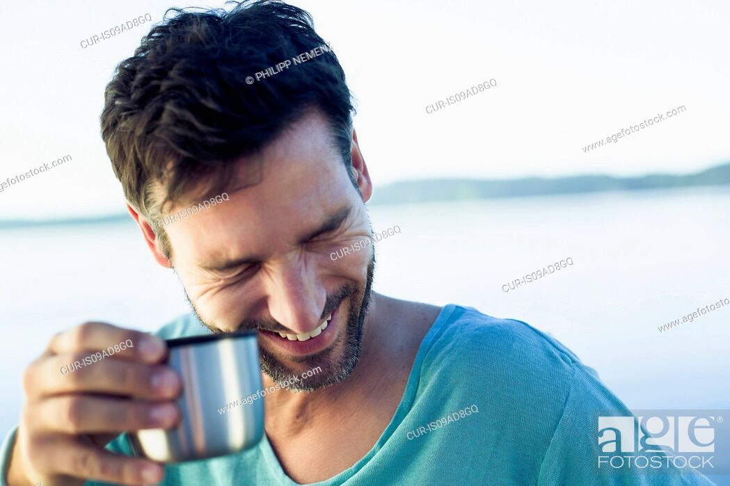 Stock Photo: Mature man with coffee, laughing.